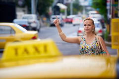 People travelling-business woman stopping yellow taxi. Blond businesswoman calling yellow taxi with arm raised in street. Tourism and business travel Stock Photo