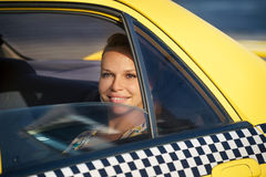 People travelling-business woman in yellow taxi. Blond woman in yellow taxi looking out of car window and smiling. Tourism and business travel Royalty Free Stock Photo