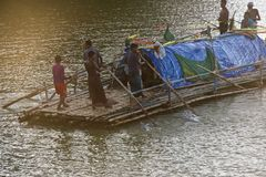 People travelling on a large boat in the river unique photo. Bangladeshi people travelling on a boat in a river at the afternoon isolated unique photo royalty free stock image