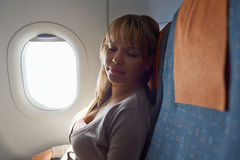 People travelling relaxed woman sleeping on plane Stock Photos