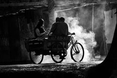 People travelling with three wheelers in a village road. Village people riding on three wheelers with the bonfire smoky environment isolated unique editorial royalty free stock image