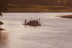 People travelling on a traditional boat in Bangladesh. Bangladeshi people are travelling on a boat in a large river unique photo stock image