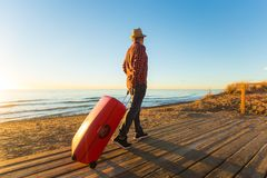 People, travelling and vacation concept - portrait of happy man walking by sea with suitcase.  stock photo