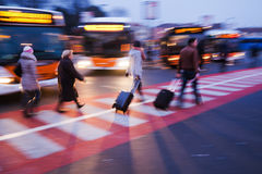 People with trollies at a bus station. People with trollies crossing the street at a bus station Stock Photo