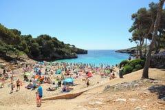 People on tropical beach, Cala dOr, Mallorca. Postcard view of a tropical beach full of people sun bathing. Taken in Cala dOr, Mallorca (Majorca Stock Photo