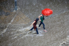 People try to cross a flooded road Stock Photos