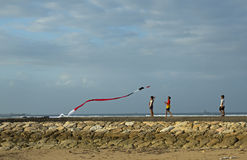 People try to fly a kite on a windy day at the Nusa Dua Beach. Bali, Indonesia - August 14, 2014: People try to fly a kite on a windy day at the Nusa Dua Beach royalty free stock photo