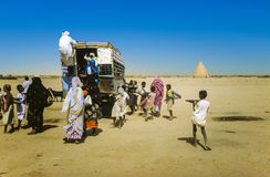 People try to get on an overland bus in Shendi Stock Photography