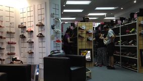 People trying new shoe at shoe store. In Richmond mall stock footage