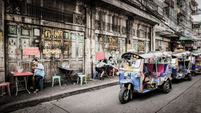 People and tuktuk taxi with background classic door in Yaowarat road,Bangkok capital city,Thailand. Bangkok, Thailand - September 9, 2016 : Unidentified people stock image