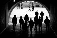 People in a tunnel. Silhouettes of people walking in an underground tunnel Stock Photo