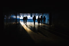 People in a tunnel. Silhouettes of people walking in an underground tunnel Royalty Free Stock Image