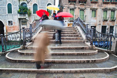 People with umbrellas crossing a bridge Stock Image