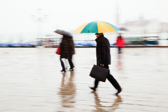 People with umbrellas on the move Stock Photo