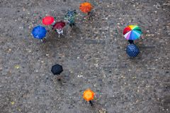 People with umbrellas on the pavement royalty free stock photos