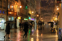 People with umbrellas in the rain. Coimbra. Portugal. People with umbrellas in the rain walking along Ferreira Borges street at night. Coimbra. Portugal Royalty Free Stock Photo