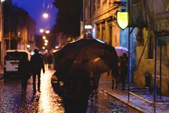 People with umbrellas in the rain in the night the old town. Shallow depth of field. Focus on umbrella Royalty Free Stock Photos