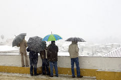 People with umbrellas in snow. A back view of several people, standing out in the snow while carrying umbrellas. Taken in Evora, Alentejo, Portugal Stock Image