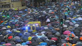 People with umbrellas walking on city street durung political meeting in Hong Kong. Adult man and woman protesters attend at demonstation in asian town on stock footage