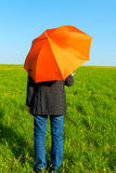 People under an orange umbrella in a field Royalty Free Stock Photo