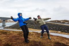 People under the strong wind. Two photographers bended under a strong gust of wind in Lofoten, winter time Royalty Free Stock Photo