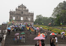 People under umbrellas. Church of St Paul. Macau. Stock Images
