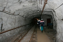 The people in the underground mine. The group of people are going in the tunnel in the underground mine Stock Photo
