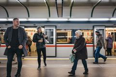 People on the underground platform in Vienna, Austria, train with open doors on the background. Vienna, Austria - November 25, 2018: People on the underground stock image