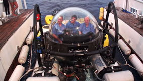 People on underwater submarine returning to ship Pacific Ocean. stock video