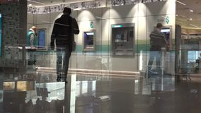 People use a cash machine  at the airport terminal stock footage