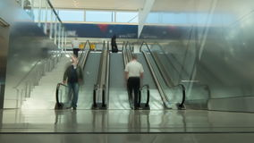 People use an escalator in airport terminal or at the mall. People`s faces are indistinguishable. A crowd of unrecognizable people or passengers with bags up and stock video