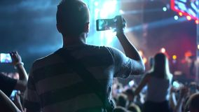 People phone music concert. People use smart phones video at music concert stock footage
