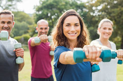 People using dumbbells. Mature people in training session of aerobics using dumbbells at park. Happy men and smiling women practicing fitness together outdoor Royalty Free Stock Photos