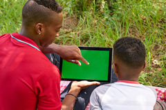 People Using Internet Email On Ipad Tablet With Green Screen. Happy black people in city park. African american family with young men and child using tablet Stock Image
