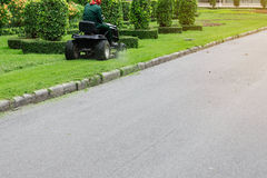People are using lawn mowers at walkways. People are using lawn mowers at walkways in garden Stock Photography