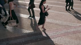 People using mobile phones while commuting to office. People busy with mobile phones while walking on city street stock footage