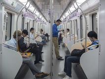 People using phones in the Metro. People connected to his tablets and smartphones. Photo taken in the Shanghai Metro stock image