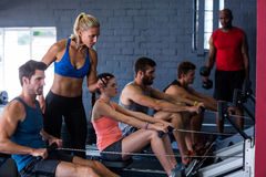 People using rowing machine with fitness instructor in gym. People using rowing machine with fitness instructor standing in gym stock images