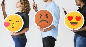 People using smartphones and holding emojis stock photography