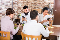 People using smartphones at restaurant table. Group of people using smartphones at restaurant table and chatting Stock Images