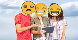 People using tablet PC with emojis over faces Stock Photos
