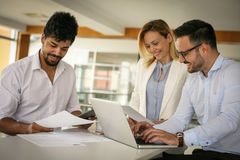 .People using technology and checking document. Business Stock Images