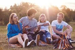 People and vacation concept. Cheerful best teenage friends enjoy romantic atmosphere on nature, have picnic together, play guitar, stock photo