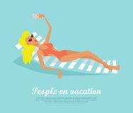 People on Vacation Girl on Deck Chair Makes Selfie. People on vacation. Woman lying on deck chair making selfie. Fashionable woman with red lips resting near the Royalty Free Stock Photo