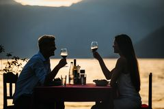 People, vacation, love and romance concept. Young couple enjoying a romantic dinner on beach. royalty free stock photos