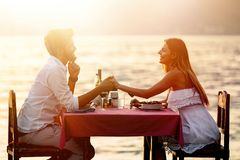 People, vacation, love and romance concept. Young couple enjoying a romantic dinner on beach. People, celebration, vacation, honeymoon and romance concept stock photography