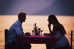 People, vacation, love and romance concept. Young couple enjoying a romantic dinner on beach. stock images