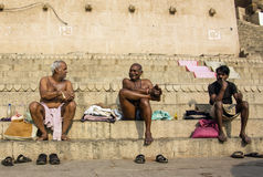 People in Varanasi. Three men sitting on the ghats of the holy city of Varanasi Stock Image