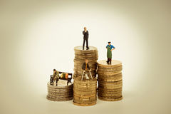 People of various social groups on pile of coins.  royalty free stock photos