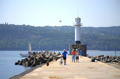 People on Varna breakwater and lighthouse Stock Image